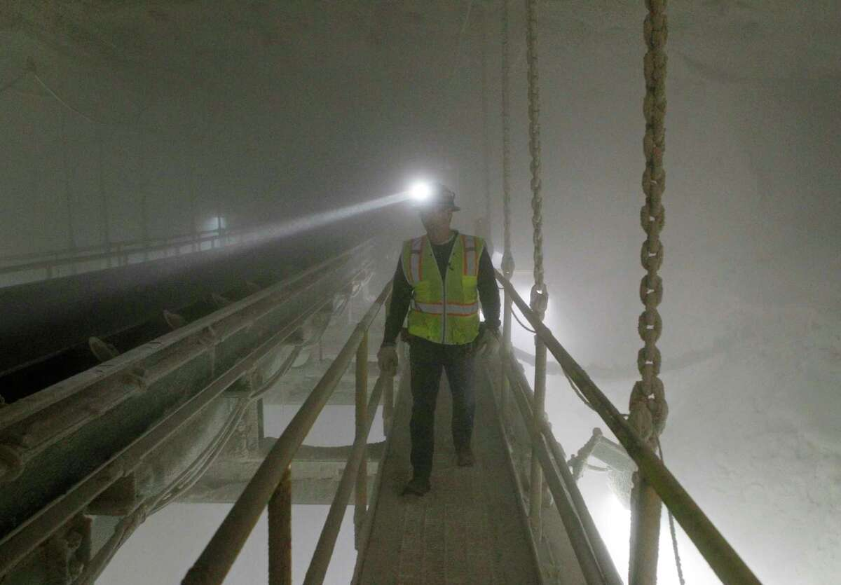 In this Jan. 27, 2017 photo, an American Rock Salt Co. mine production worker inspects the surge bin at the mine in Hampton Corners, N.Y. Deep below upstate New York?'s farm country, workers in ghostly tunnels are praying for snow. Fiercer winters mean better business, longer hours and fatter paychecks at what?'s billed as the nation?'s most productive salt mine, which ships trainloads of snow-melting road salt to municipalities across the Northeast. (AP Photo/Jeffrey T. Barnes) ORG XMIT: NYJB107