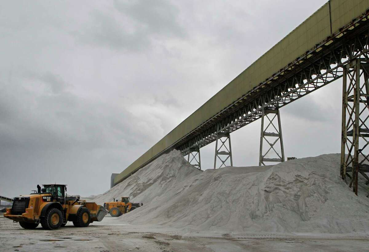 In this Jan. 27, 2017 photo, American Rock Salt Co. loaders work a road salt pile at the mine in Hampton Corners, N.Y.  Fiercer winters mean better business, longer hours and fatter paychecks at what?'s billed as the nation?'s most productive salt mine, which ships trainloads of snow-melting road salt to municipalities across the Northeast. (AP Photo/Jeffrey T. Barnes)