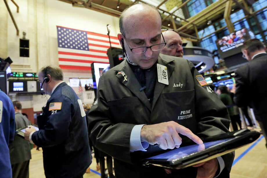 Trader Andrew Silver-man works Friday on the floor of the New York Stock Exchange. Photo: Richard Drew, STF / AP