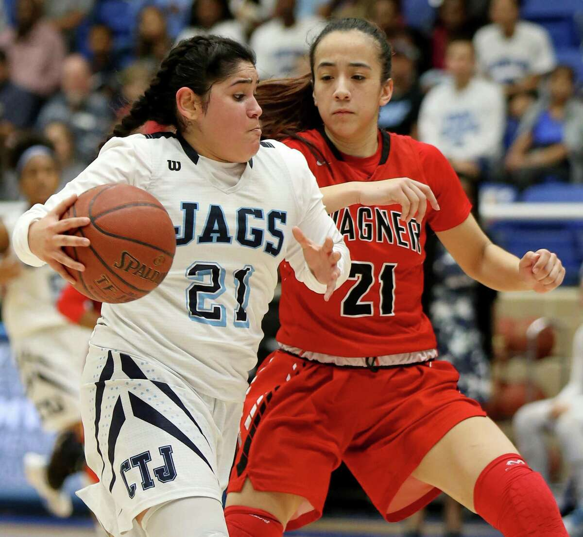 Johnson's Alina Falcon drives around Wagner's Toni Cuellar during second half action of their Class 6A second round girls basketball playoff game held Friday Feb. 17, 2017 at the Northside Sports Gym. Johnson won 72-61.