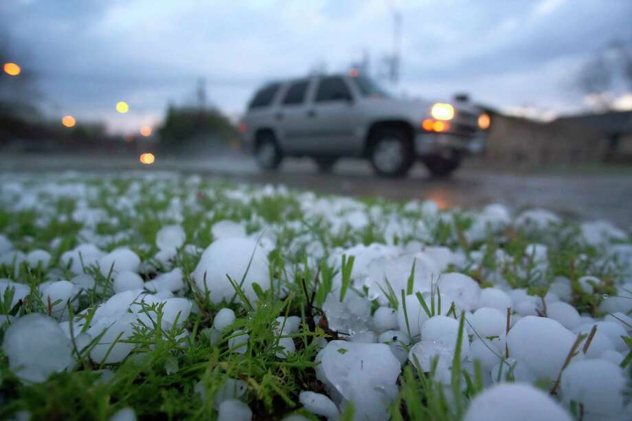 A vehicle drives by a field covered from a hail storm early Thursday, March 17, 2016 in Fort Worth, Texas.  Hail the size of golf balls coated parts of North Texas, broke windows, damaged police vehicles and killed exotic birds at the Fort Worth Zoo.   (Rodger Mallison/Star-Telegram via AP)  MAGS OUT; (FORT WORTH WEEKLY, 360 WEST); INTERNET OUT; MANDATORY CREDIT Photo: Rodger Mallison, MBI / Star-Telegram
