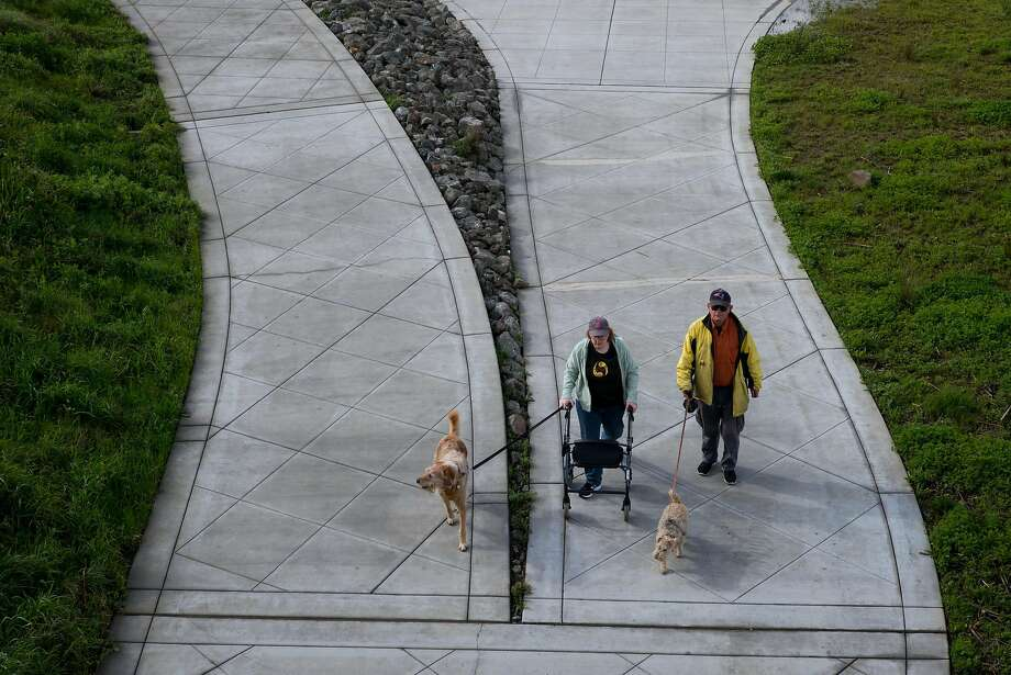Strollers stroll through the Oxbow Commons, a city park that double as a bypass for the flood-prone Napa River. The park passed the test during recent storms. Photo: James Tensuan, Special To The Chronicle