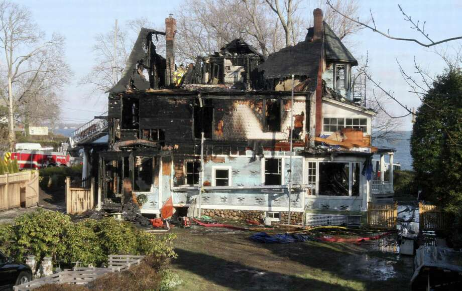 FILE - In this Dec. 25, 2011 file photo, firefighters investigate a house in Stamford, Conn., where an early morning fire left five people dead. The Hartford Courant reported Monday, May 9, 2016, that in a lawsuit deposition, contractor Michael Borcina said he lied to protect the children's mother Madonna Badger, who was the one who left a bag of fireplace ashes in a mudroom, which were suspected of causing the fire. (AP Photo/Tina Fineberg, File) Photo: Tina Fineberg / Associated Press / AP2011
