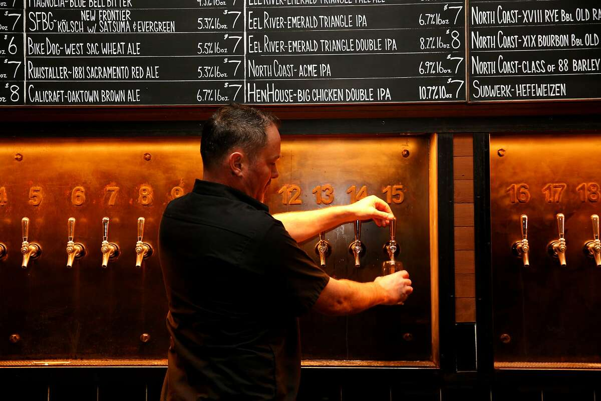 Jon Guinea, owner of Hopwater Distribution, pours a Big Chicken Double IPA for a customer on Friday, Feb. 17, 2017, in San Francisco, Calif. A keg of newly released Big Chicken Double IPA from HenHouse Brewery was available on tap.