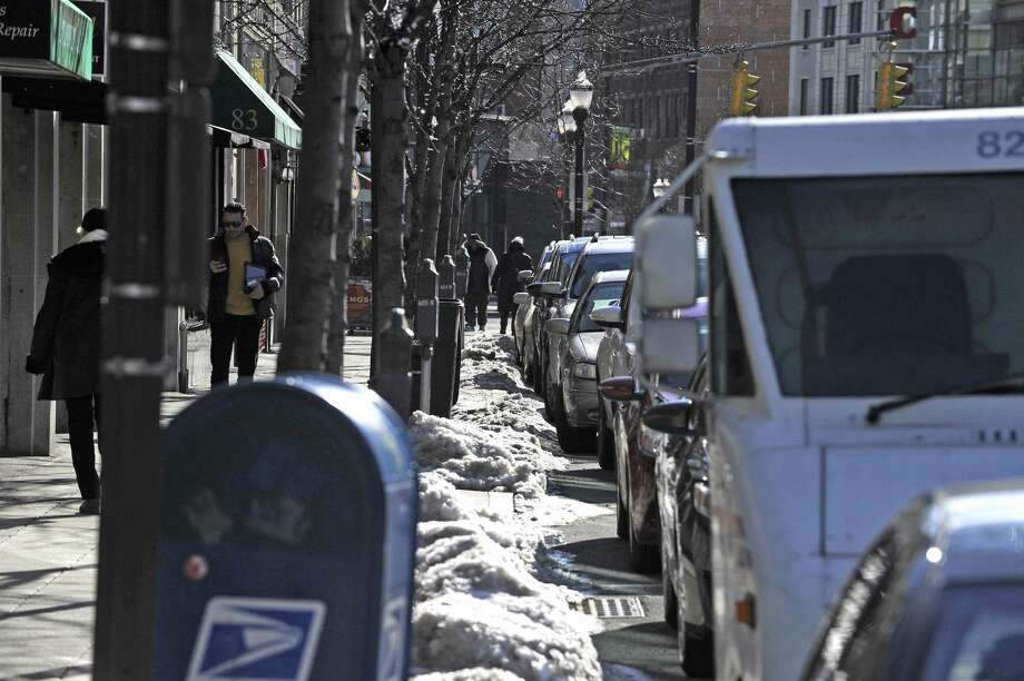 Pedestrians make there way along Bedford Street in Stamford on Feb. 16, 2017. Parking is at a premium, with limited spaces available, drivers often double park in the street as they wait for a parking space to open up. Photo: Matthew Brown / Hearst Connecticut Media / Stamford Advocate