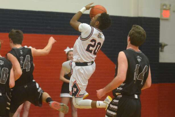 Plainview's Carlton Searcy goes in for a layup between two defenders during a game earlier this season.