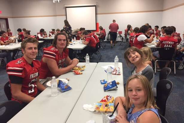 Huffman football players and their buddies in a dinner as part of the Falcons Leading Youth (FLY) program last year, which became the pals program