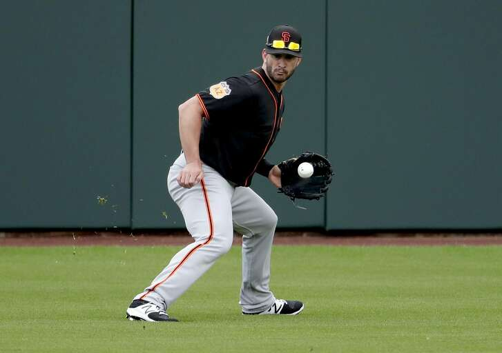 San Francisco Giants' Justin Ruggiano fields a ball during spring training baseball workouts, Friday, Feb. 17, 2017, in Scottsdale, Ariz. (AP Photo/Matt York)