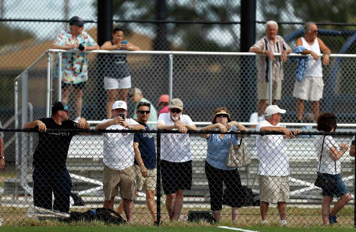 Fans perch along the fence and up in the stands to get a look as the Houston Astros took the field during spring training at The Ballpark of the Palm Beaches, in West Palm Beach, Florida, Saturday, February 18, 2017.