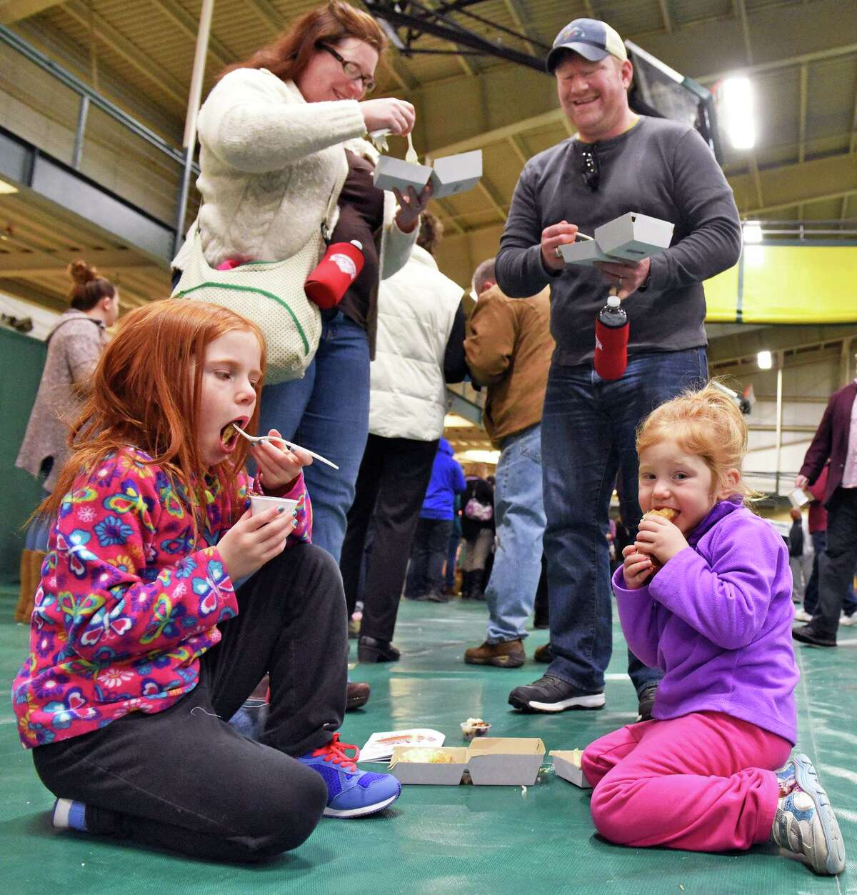 Elizabeth and Tim Dunn of Malta and daughters Evelyn, 7, left, and Maureen, 4, taste the offerings at the 8th Annual Mac-n-Cheese Bowl Saturday Feb. 18, 2017 in Colonie, NY. (John Carl D'Annibale / Times Union)