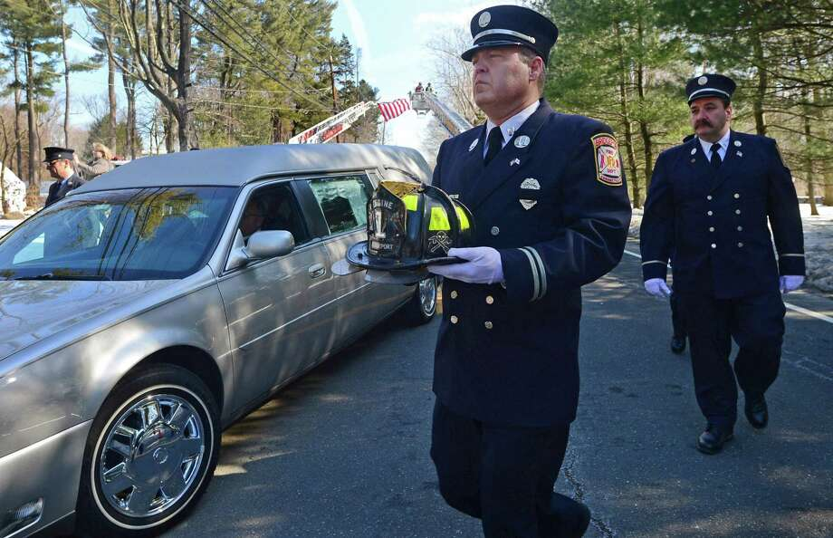A Bridgeport firefighter carries a helmet in honor of Phil Reeves, a long time Wilton resident, U.S. Army veteran, and professional firefighter who served the Westport and Bridgeport communities, during a funeral procession Saturday, February 18, 2017, outside at St. Matthew's Church on New Canaan Road, in Wilton, Conn. Photo: Erik Trautmann / Hearst Connecticut Media / Norwalk Hour