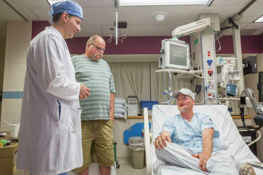 Andy Sandness, right, talks with his father, Reed Sandness, and Dr. Samir Mardini, left, before Andy's face transplant procedure at the Mayo Clinic in Rochester, Minn.  Photo: Eric M. Sheahan, HONS / Mayo Clinic
