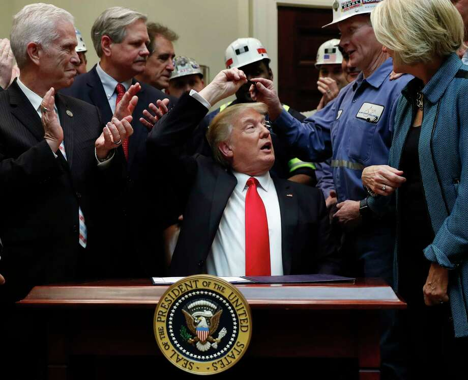 In this Feb. 16, 2017 photo, President Donald Trump hands the pen he used to sign H.J. Res. 38 to Kevin Hughes, General Manager, Murray Energy Corporation, second from right, in the Roosevelt Room of the White House in Washington. The president is surrounded by coal miners and members of congress including Sen. Shelley Moore Capito, R-W.Va., right, Rep. Bill Johnson, R-Ohio, left, and Rep. Jim Renacci, R-Ohio. third from left, (AP Photo/Carolyn Kaster) Photo: Carolyn Kaster, STF / Copyright 2017 The Associated Press. All rights reserved.