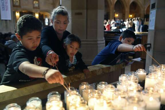 Veronica Cardenas lights candles at the Shrine of Saint Jude Thaddeus, the Patron Saint of Hope, with her children Oscar, Makayla and Pedro (right) at Saint Dominic's Catholic Church in San Francisco, Calif. on Saturday, Feb. 18, 2017. Many people are turning to prayers as a way of relieving post-election stress.