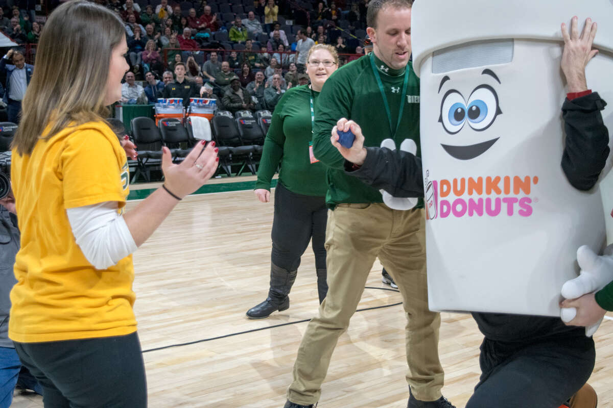 Steve Duckett, dressed as the Dunkin' Donuts mascot, prepares to reveal his identity to his girlfriend Erin Tobin, for a surprise proposal at Siena's men's basketball game against Manhattan. (Courtesy of Siena College)