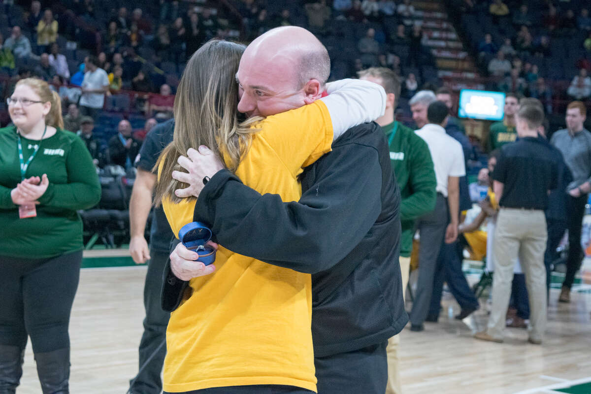 Steve Duckett hugs his girlfriend, Erin Tobin, after his surprise proposal at Siena's men's basketball game against Manhattan, after Erin made a halfcourt shot during a Dunkin' Donuts promotion. (Courtesy of Siena College)