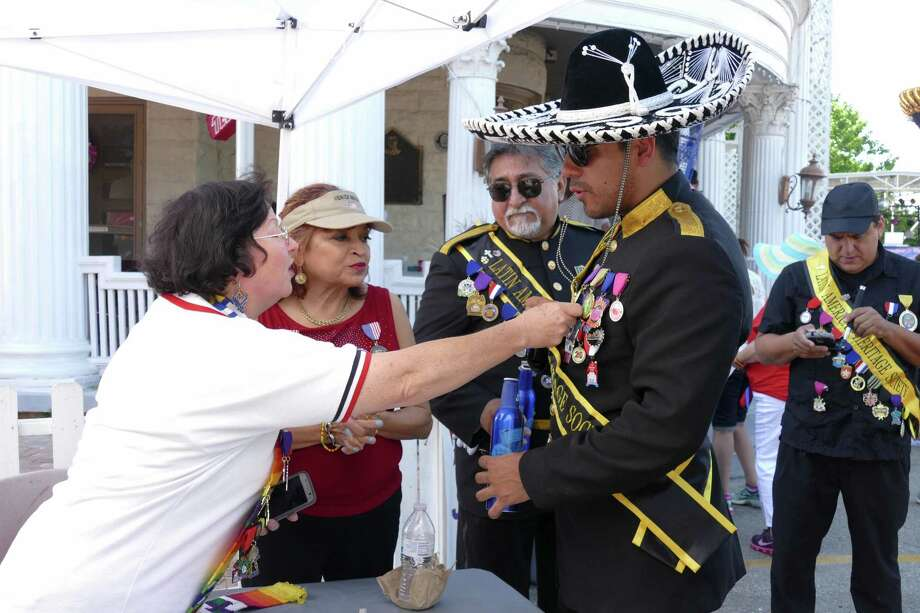 Karen Morgan, who is retired from the Air Force, inspects Fiesta medals on the chest of Latin American Heritage Society member Girien Salazar at VFW Post 76 during the 10th Street River Festival on Saturday, April 23, 2016. Proceeds from the event will help maintain the VFW's historic building and fund veteran programs. Photo: Billy Calzada, Staff / San Antonio Express-News / San Antonio Express-News
