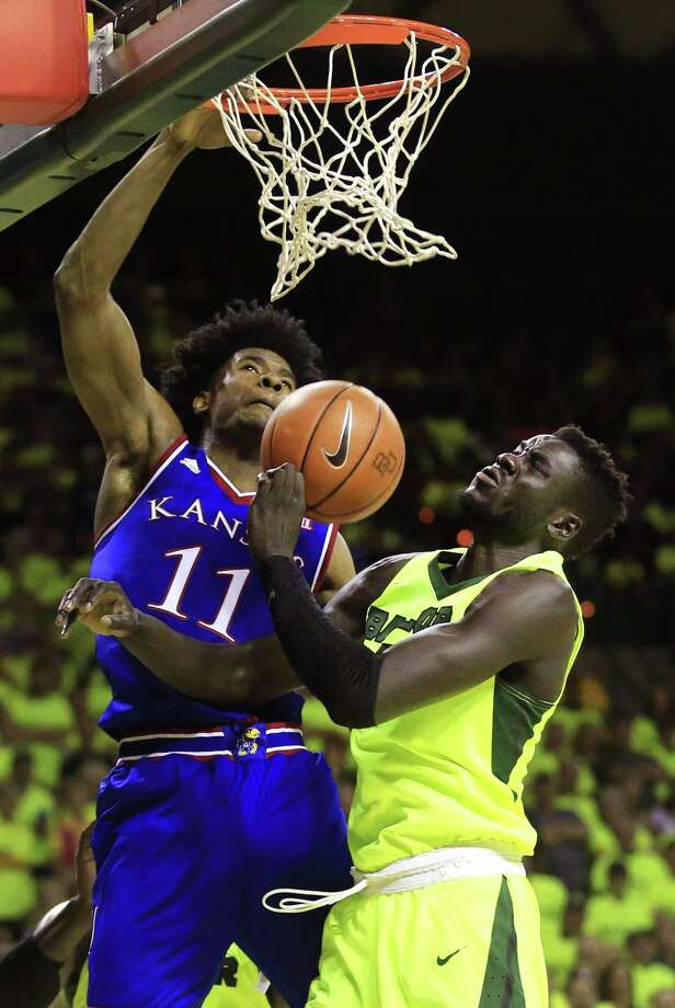 Kansas' Josh Jackson, left, slams one home in the second half as Baylor's Jo Lual-Acuil Jr. gets a close-up view of the action at Waco's Ferrell Center on Saturday. Photo: Ron Jenkins, Stringer / 2017 Getty Images