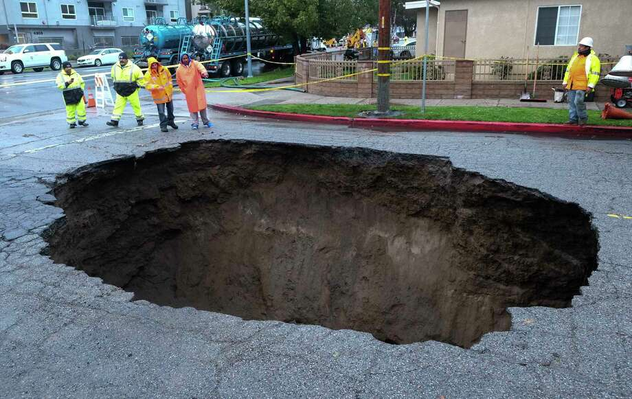 Inspectors examine a sinkhole Saturday, Feb. 18, 2017, in Studio City, north of Los Angeles, Calif, Calif. Two vehicles fell into the 20-foot sinkhole on Friday night and firefighters had to rescue one woman who escaped her car but was found standing on her overturned vehicle.  (AP Photo/Ringo H.W. Chiu) Photo: Ringo H.W. Chiu, FRE / FR170512 AP