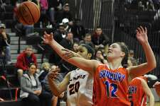 Danbury's Catrina Sullivan (12) and Stamford's Marthe Guirand (20) fight for the ball in the FCIAC girls basketball quarterfinal game between Danbury and Stamford high schools, Saturday, February 18, 2017, at Ridgefield High School, in Ridgefield, Conn.