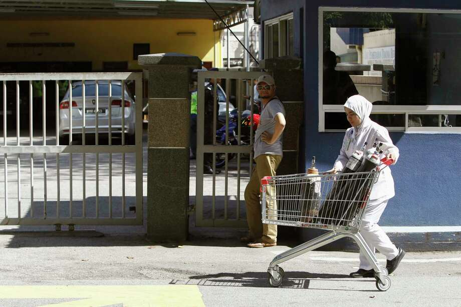 A medical staff member pushes a trolley in front the main gate to the forensic department at Kuala Lumpur Hospital in Kuala Lumpur, Malaysia Saturday, Feb. 18, 2017. Malaysia performed a second autopsy on the estranged half brother of North Korea's leader because the first procedure was inconclusive, piling on the intrigue surrounding what appeared to be a well-executed assassination at an airport in Kuala Lumpur, an official said Saturday. Police also arrested a fourth suspect, identified as a North Korean man. (AP Photo/Daniel Chan) Photo: Daniel Chan, STR / Copyright 2017 The Associated Press. All rights reserved.