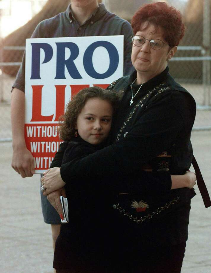 """FILE - In this Jan. 22, 1997, file photo, Norma McCorvey, right, known as Jane Roe in the landmark U.S. Supreme Court ruling 24 years ago that legalized abortion nationwide, stands with her friend Meredith Champion, 9, at an Operation Rescue rally in downtown Dallas. Norma McCorvey, the """"Jane Roe"""" at the center of the 1973 U.S. Supreme Court decision that legalized abortion, has died. She was 69. Journalist Joshua Prager, who is working on a book about McCorvey, says she died Saturday, Feb. 18, 2017, morning at an assisted living centre in Katy, Texas. Although McCorvey was the plaintiff in Roe v. Wade, she later became an anti-abortion activist. (AP Photo/Ron Heflin, File) Photo: Ron Heflin, STF / Associated Press / AP1997"""