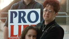 "FILE - In this Jan. 22, 1997, file photo, Norma McCorvey, right, known as Jane Roe in the landmark U.S. Supreme Court ruling 24 years ago that legalized abortion nationwide, stands with her friend Meredith Champion, 9, at an Operation Rescue rally in downtown Dallas. Norma McCorvey, the ""Jane Roe"" at the center of the 1973 U.S. Supreme Court decision that legalized abortion, has died. She was 69. Journalist Joshua Prager, who is working on a book about McCorvey, says she died Saturday, Feb. 18, 2017, morning at an assisted living centre in Katy, Texas. Although McCorvey was the plaintiff in Roe v. Wade, she later became an anti-abortion activist. (AP Photo/Ron Heflin, File)"