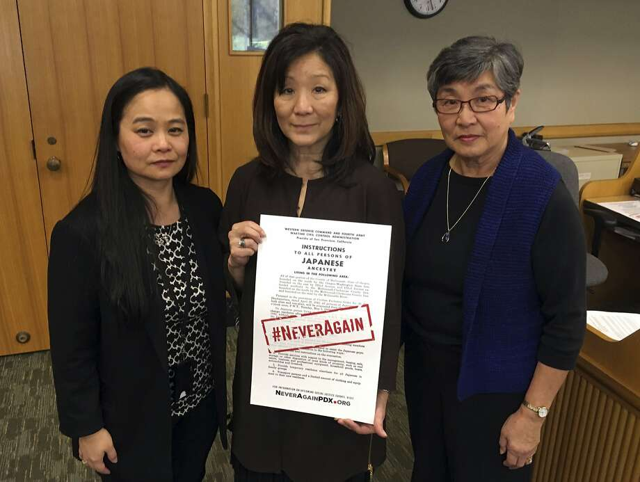 In a hearing room of the Oregon State Capitol, Carol Suzuki (left), Lynn Fuchigami Longfellow and June Arima Schumann display a copy of a poster marking ceremonies commemorating the internment of Japanese Americans during World War II. Photo: Andrew Selsky, Associated Press