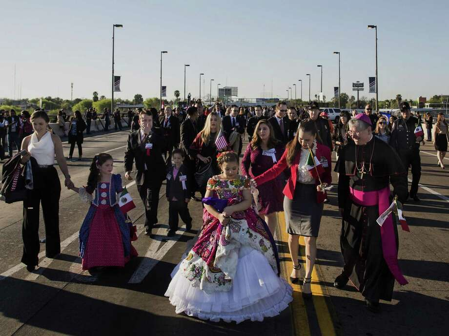 Ella Alessandra Gonzalez, one of the abrazo children representing the United States, left, looks at Cassandra Cabrera Zamudio, center, one of the abrazo children representing Mexico, as they walk to the American side of the Juarez-Lincoln International Bridge after the International Bridge Ceremony during the 120th Annual Washington's Birthday Celebration in Laredo, Texas on February 18, 2017. Photo: Carolyn Van Houten, Staff / San Antonio Express-News / 2017 San Antonio Express-News