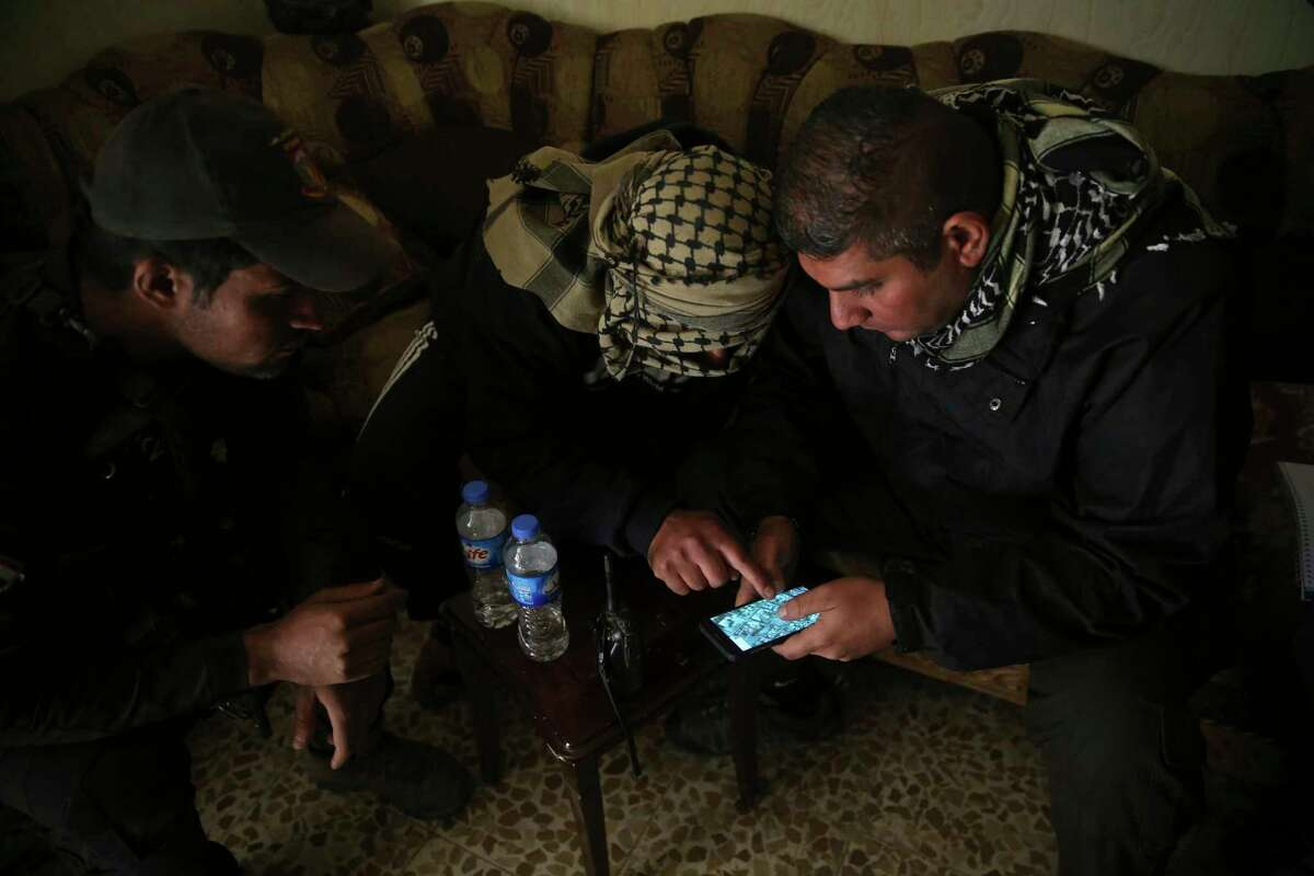 FILE - In this Nov. 25, 2016 photo, Special forces Lt. Col. Ali Hussein, right, listens to an Iraqi informant, center, giving information about Islamic State militant positions on a mobile map, in the Bakr front line neighborhood, in Mosul, Iraq. More than 300 people inside Mosul have worked as informants for Iraqi intelligence, passing on information about Islamic State militants, a major boost in the battle to retake the city. (AP Photo/Hussein Malla, File) ORG XMIT: CAIMA501