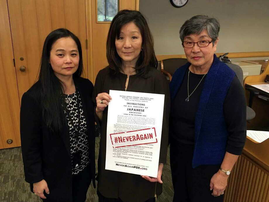 Carol Suzuki, Lynn Fuchigami Longfellow, middle and June Arima Schumann on Monday, Feb. 13, 2017, display a copy of a poster in a hearing room in the Oregon State Capitol that notified Japanese-Americans they would be sent to relocation camps. The slogan #NeverAgain has been emblazoned on the poster. Seventy-five years ago, America's president signed an executive order that incarcerated 120,000 Japanese Americans. Now, the survivors, descendants and activists are backing a bill in the Oregon Legislature to make the anniversary a Day of Remembrance, underscoring that this should never happen again, against any group. (AP Photo/Andrew Selsky) ORG XMIT: RPAS901 Photo: Andrew Selsky / Copyright 2017 The Associated Press. All rights reserved.