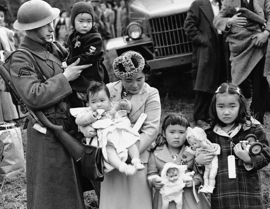FILE - In this March 30, 1942 file photo, Cpl. George Bushy, left, a member of the military guard which supervised the departure of 237 Japanese people for California, holds the youngest child of Shigeho Kitamoto, center, as she and her children are evacuated from Bainbridge Island, Wash. Roughly 120,000 Japanese immigrants and Japanese-Americans were sent to desolate camps that dotted the West because the government claimed they might plot against the U.S. (AP Photo/File) ORG XMIT: NY542 / Copyright 2017 The Associated Press. All rights reserved.