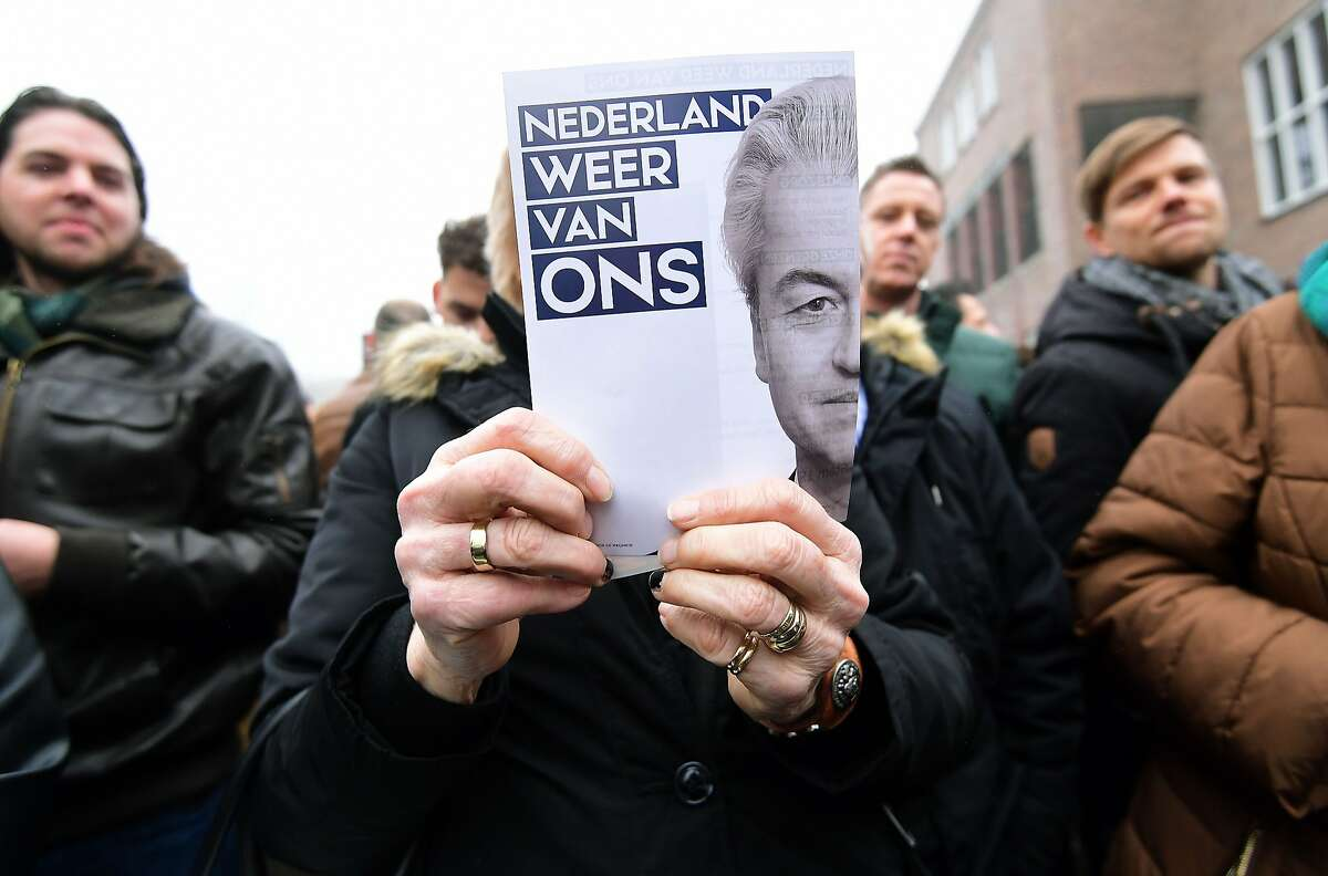 """Supporters of Dutch far-right politician and leader of the Partij Voor De Vrijheid (PVV or Freedom Party) Geert Wilders hold leaflets bearing his image and a slogan that translates to """"Make Netherlands ours again."""""""
