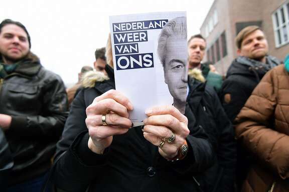 "Supporters of Dutch far-right politician and leader of the Partij Voor De Vrijheid (PVV or Freedom Party) Geert Wilders hold leaflets bearing his image and a slogan which translates as ""Make Netherlands ours again"", as he officially launches his parliamentary election campaign in Spijkenisse on February 18, 2017.  Firebrand Dutch anti-Islam MP Geert Wilders launched his election campaign  with a stinging attack on the country's Moroccan population, saying he wanted to give The Netherlands back to the ""Dutch people"".    / AFP PHOTO / EMMANUEL DUNANDEMMANUEL DUNAND/AFP/Getty Images"