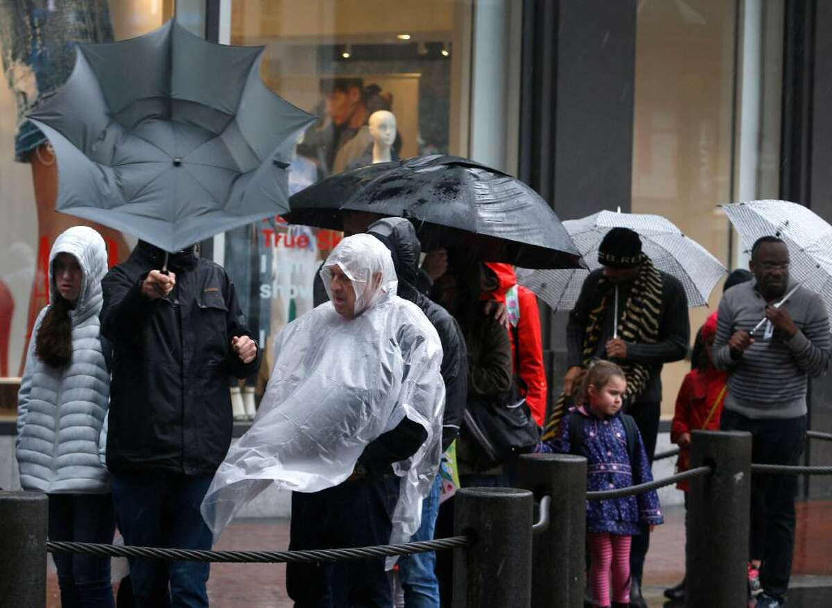 People wait to board a cable car at Powell and Market streets in heavy wind and rain in San Francisco on Friday. Another powerful system is on track to hit the region.
