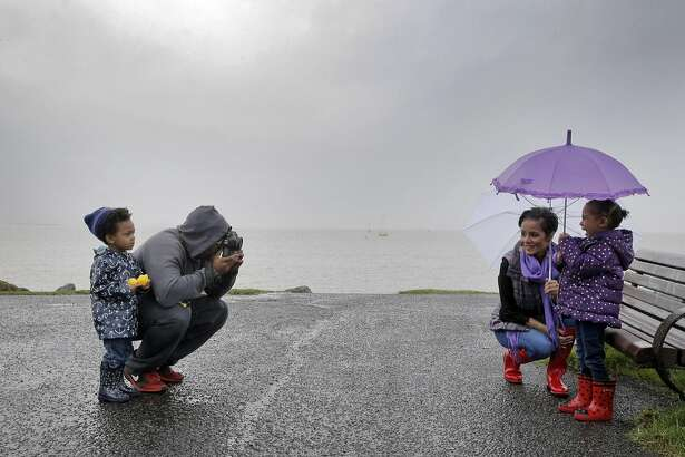 Jaiden Notes, 2, left, watches as his dad, Anthony Notes takes a photo of Haley Hayes, and her daughter Harper Groce, 4, during a break in the rain at Cesar Chavez Park in Berkeley, Calif., on Sunday, February 19, 2017. The Bay Area is preparing for a heavy storm that should last through Monday.