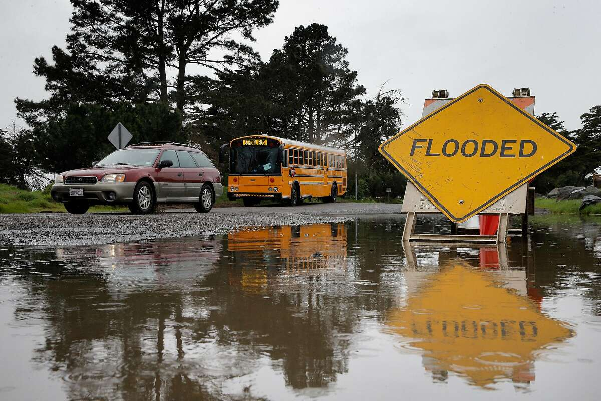 A car passes by a flooded part of Spinnaker Road during a break in the rain near Cesar Chavez Park in Berkeley, Calif., on Sunday, February 19, 2017. The Bay Area is preparing for a heavy storm that should last through Monday.