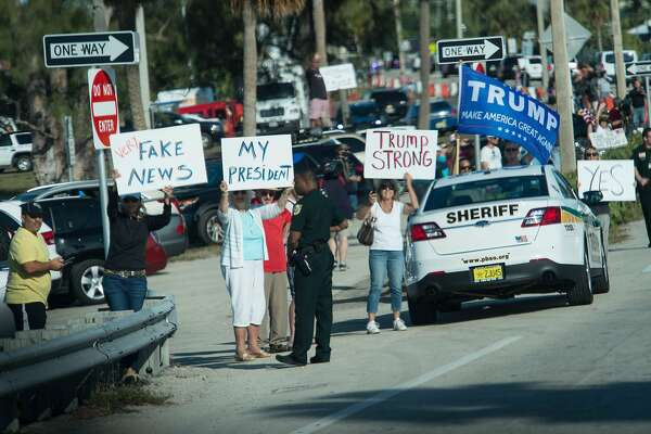 Supporters of US President Donald Trump hold signs as his motorcade drives by in Palm Beach, Florida, near his Mar-a-Lago resort on February 17, 2017. / AFP PHOTO / NICHOLAS KAMMNICHOLAS KAMM/AFP/Getty Images
