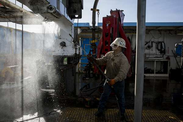 Danny Perez, a floor hand, washes the rig with water at Latshaw Drilling's Oil Rig 43 in Midland, Texas, Feb. 8, 2017. The rig is two years old, and requires a smaller crew to run it because of advancing technologies. (Ilana Panich-Linsman/The New York Times)