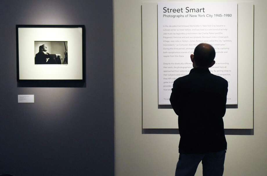 "A man reads the exhibition statement of the new ""Street Smart"" photography exhibit beside Herman Leonard's 1950 photograph of Tony Bennett at the Bruce Museum in Greenwich, Conn. Sunday, Feb. 19, 2017. The display features photographs of New York City from 1945 to 1980 by Larry Fink, Herman Leonard, Leon Levinstein, John Shearer, and Garry Winogrand. Street Smart provides ""a glimpse at life in the city during the post-war period and at how street-savvy New Yorkers navigated its bustling landscape."" Photo: Tyler Sizemore / Hearst Connecticut Media / Greenwich Time"