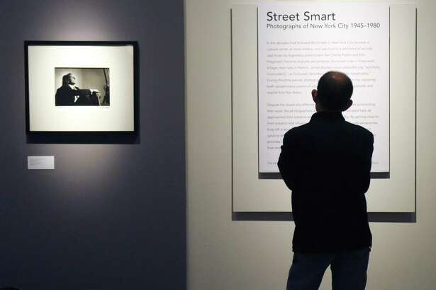 "A man reads the exhibition statement of the new ""Street Smart"" photography exhibit beside Herman Leonard's 1950 photograph of Tony Bennett at the Bruce Museum in Greenwich, Conn. Sunday, Feb. 19, 2017. The display features photographs of New York City from 1945 to 1980 by Larry Fink, Herman Leonard, Leon Levinstein, John Shearer, and Garry Winogrand. Street Smart provides ""a glimpse at life in the city during the post-war period and at how street-savvy New Yorkers navigated its bustling landscape."""