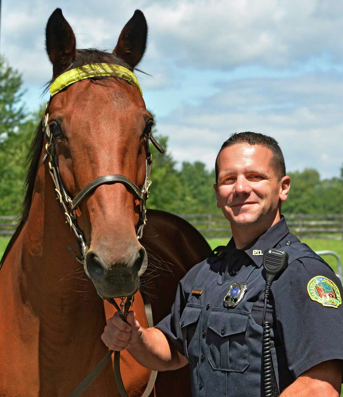 Saratoga Police officer Glenn Barrett stands with his partner, 18-year-old Jupiter, Thursday afternoon Aug. 14, 2014, in Saratoga Springs, N.Y. (Skip Dickstein/Times Union)