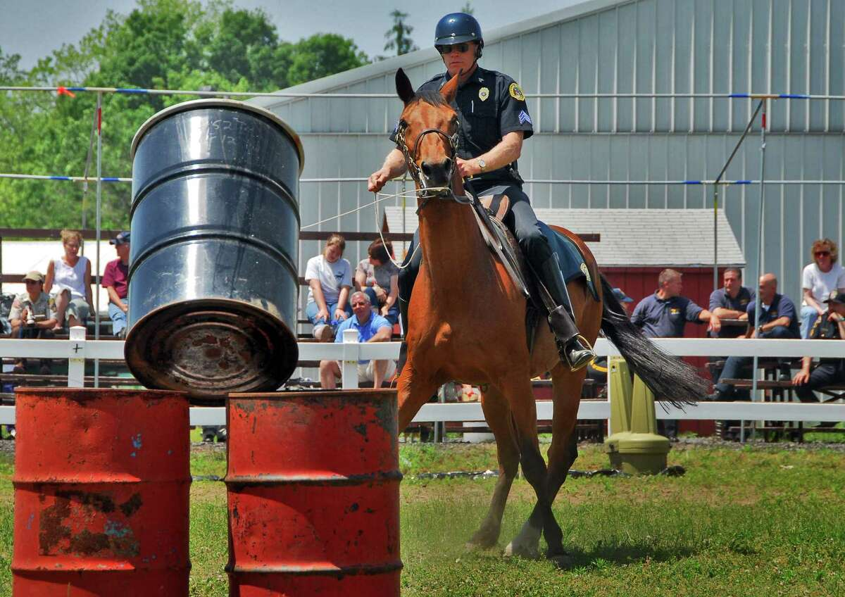 Saratoga Springs Police Sgt. Michael Chowske, aboard Jupiter, runs the obstacle course during mounted unit competition, part of the state police and fire games at the Ballston Spa Fairgrounds Friday June 16, 2006. (John Carl D'Annibale/Times Union)