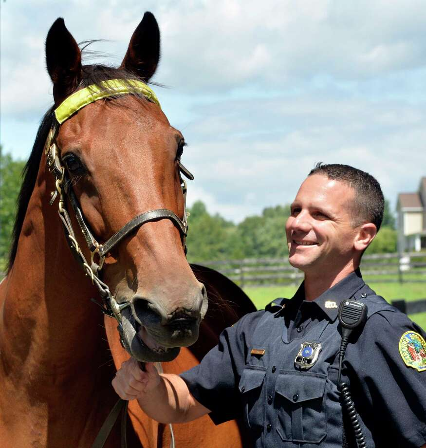 Saratoga Police officer Glenn Barrett stands with his partner, 18-year-old Jupiter, Thursday afternoon Aug. 14, 2014, in Saratoga Springs, N.Y.    (Skip Dickstein/Times Union) Photo: SKIP DICKSTEIN / 00028166A