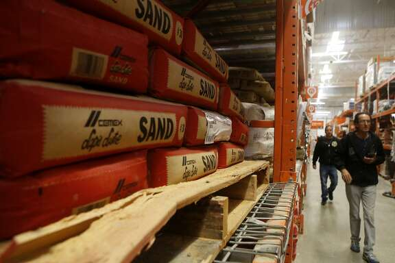 Customers walk by 50 pound bags of  Cemex Lapis Lustre Cemex sand that is found on the shelves of Home Depot on Sunday, Feb. 19, 2017, in Colma, Calif. This sand is from the last sand dredging operation to take place in Monterey Bay, California.