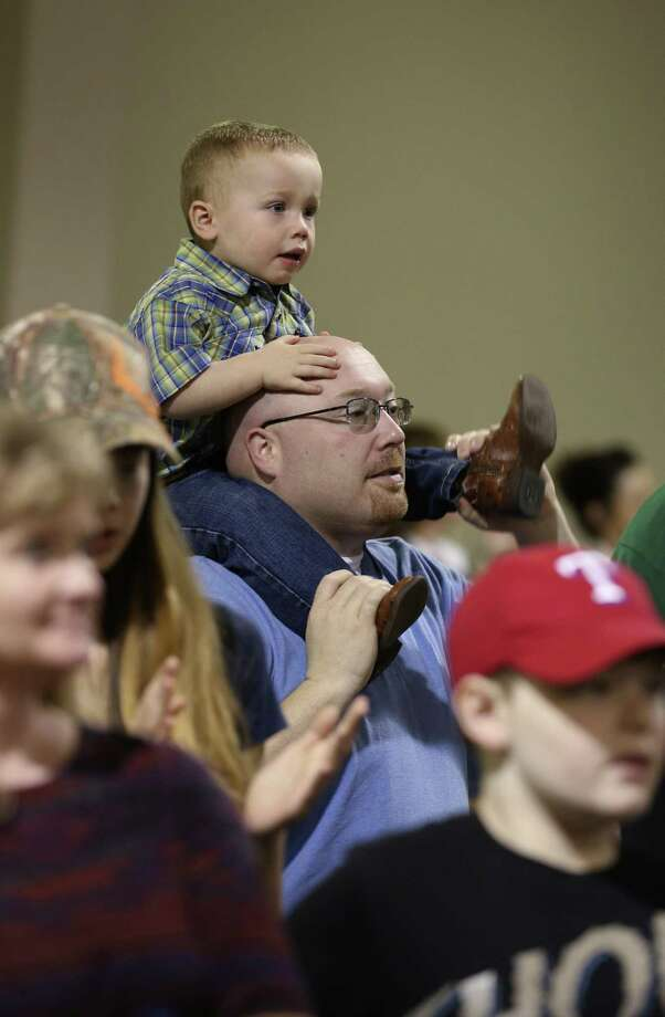 Two-year-old Tyson Braden, gets a higher view on top of his dad, John, shoulders during Cowboy Church at the San Antonio Stock Show and Rodeo, Sunday, Feb. 19, 2017. Cowboy Church is held every Sunday morning during the stock show's 18-day run. The speaker for the non-denominational service was San Antonio Spurs Co-Chaplain Rich Garza. Photo: JERRY LARA, Staff / San Antonio Express-News / © 2017 San Antonio Express-News