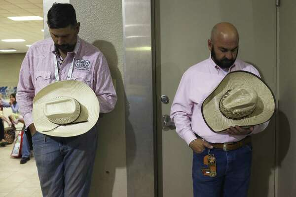 Tony Quinters (left) and Jay Strawn bow their heads in prayer during Cowboy Church at the San Antonio Stock Show & Rodeo on Feb. 19. Cowboy Church is held every Sunday morning during the stock show's 18-day run. The final service is this coming Sunday.
