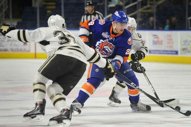 Kellen Jones of the Sound Tigres is converged on by Hershey defenders Hubert Labrie, left, and Riley Barber as he carries the puck across center ice during their AHL hockey game at the Webster Bank Arena in Bridgeport on Sunday.
