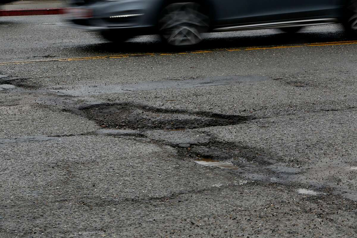 Potholes can be found on the roads around International Blvd. and 14th St. on Sunday, Feb. 19, 2017, in Oakland. Roads throughout the Bay Area are slowly improving, according to a new report, and officials at the Metropolitan Transportation Commission are crediting an infusion of SB1 gas tax dollars for the gradual upward trend.