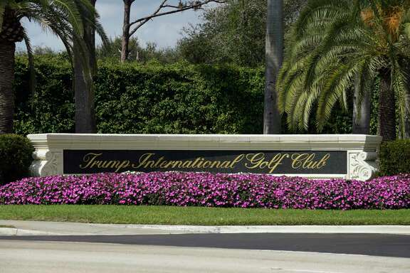 Flowers frame the front of the sign for the Trump International Golf Club in West Palm Beach, Fla., Sunday, Feb. 19, 2017, while President Donald Trump is at the club. (AP Photo/Susan Walsh)